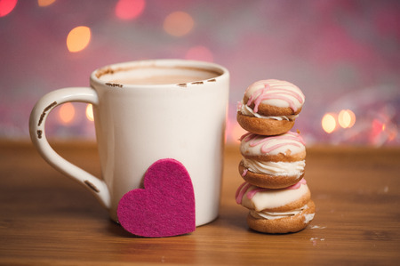 Cup of coffee with cakes and felt heart stay on wooden table over christmas lights. Selective focus. Stock Photo