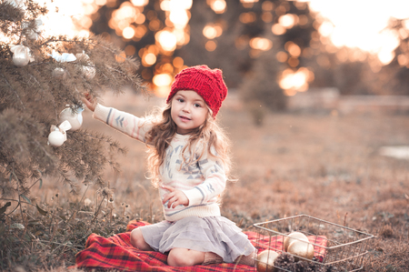 Cute kid girl 4-5 year old decorating Christmas tree outdoors. Wearing knitted hat, sweater and skirt. Looking at camera. Stock Photo