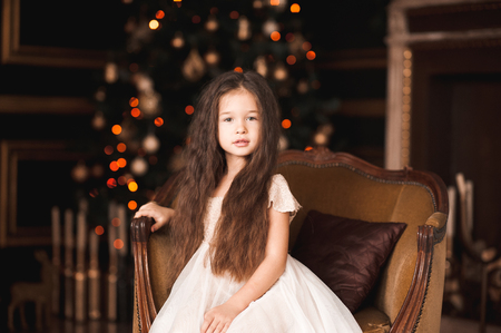 Cute baby girl 4-5 year old sitting in retro armchair over Christmas tree in room. Looking at camera. Childhood.