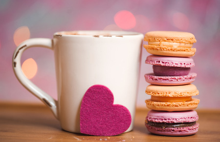 Cup of coffee with macaroons cookies and pink heart on wooden table over christmas lights. Selective focus.