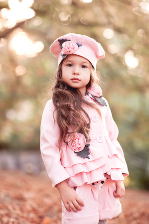 Cute baby girl 4-5 year old wearing stylish winter jacket, shorts and hat outdoors. Looking at camera. Childhood. Autumn season.