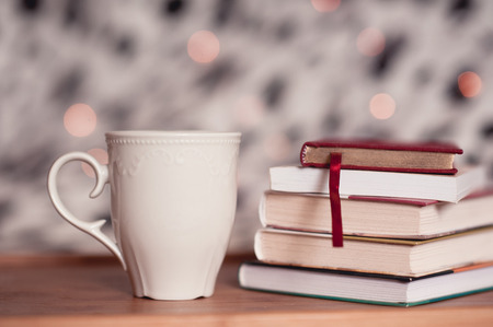 warm things: Cup of tea staying with stack of books on wooden table over christmas lights