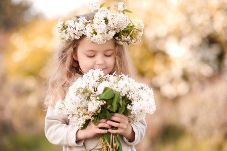 hairband: Smiling kid girl 4-5 year old holding white lilac flowers outdoors.