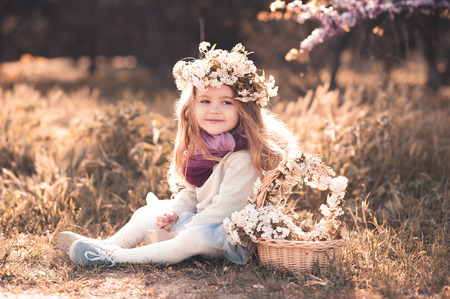 Smiling baby girl 4-5 year old wearing stylish clothes and floral hairband sitting outdoors. Childhood.  Stock Photo