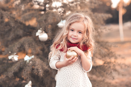 Funny baby girl wearing knitted scarf and shirt holding glitter christmas ball standing over christmas tree outdoors.Looking at camera. Posing outdoors. Holidays time. Childhood. Archivio Fotografico