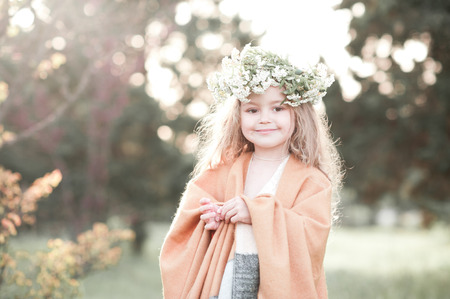 3 4 years: Smiling baby girl 3-4 year old wearing flower wreath outdoors. Looking at camera.