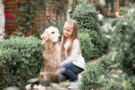 Cute baby girl 3-4 year old holding labrador pet outdoors. Togetherness. Friendship.  Stock Photo