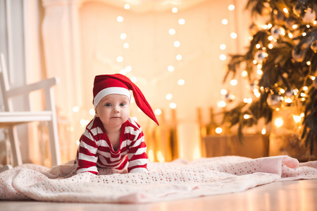 Cute baby girl wearing santa claus suit crawling on floor over Christmas lights. Looking at camera. Holiday season.  Stock Photo