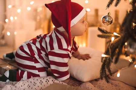 Baby girl 1 year old crawling under Christmas tree wearing body suit in red and white color. Looking at Christmas ball. Holiday season.  Stock Photo