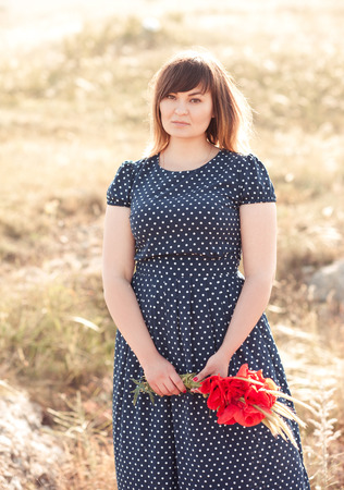 Beautiful blonde girl 20-24 year old holding poppies outdoors. Wearing stylish dress. Looking at camera.