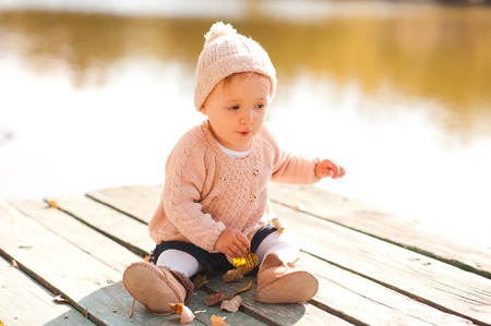 12 year old: Cute baby girl 1-2 year old sitting on wooden pier playing with autumn leaves outdoors. Childhood.  Stock Photo