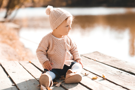 12 year old: Stylish baby girl 1-2 year old wearing knitted sweater and hat sitting on wooden pier outdoors.Looking away. Childhood. Autumn season. Stock Photo