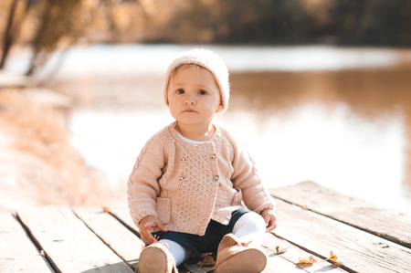 12 year old: Cute baby girl 1-2 year old wearing stylish knitted clothes outdoors. Looking at camera. Autumn season.  Stock Photo