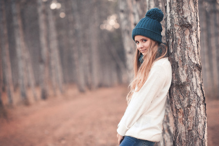 blonde teenager: Stylish teen girl 14-16 year old wearing white knitted sweater and blue knitted hat posing in forest outdoors. Looking at camera. Winter season.