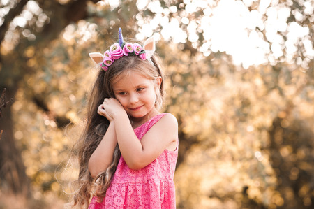 hairband: Smiling baby girl 4-5 year old wearing unicorn hairband and pink dress outdoors. Childhood.
