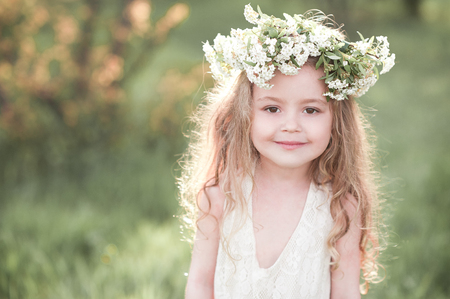 Smiling baby girl 4-5 year old wearing white dress and flower hairband over nature background. Looking at camera. Childhood.