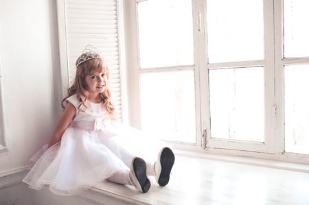 windowsill: Smiling kid girl princess 5-6 year old wearing stylish white dress and crown sitting on windowsill in room. Looking at camera. Celebrating birthday.  Stock Photo