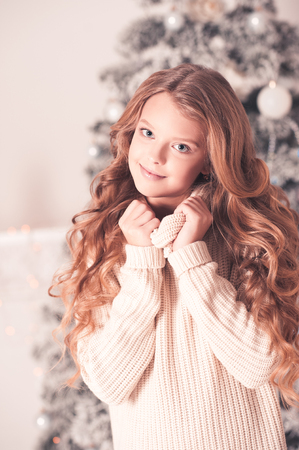Smiling teenage girl with long blonde curly hair wearing cozy knitted sweater over Christmas tree in room. Looking at camera. Stock Photo