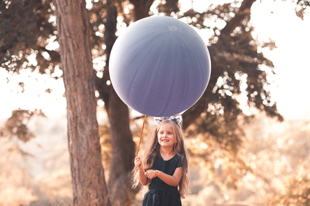 huge: Cute kid girl 4-5 year old holding big balloon outdoors. Smiling child girl. Wearing stylish dark blue dress. Childhood.