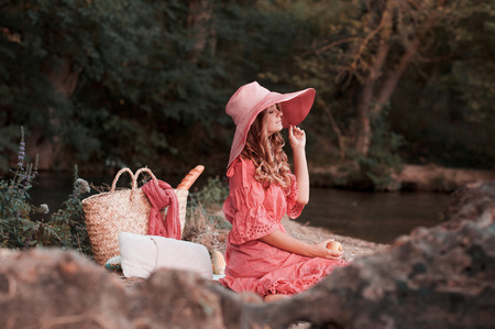 20s: Smiling girl wearing stylish pink dress and hat. Making picnic outdoors. 20s.