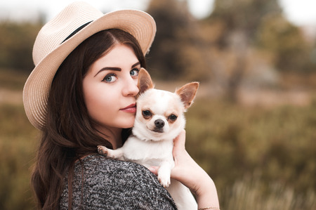 Beautiful young girl 20-24 year old holding pet dog chihuahua outdoors. Looking at camera. Togetherness. Stock Photo