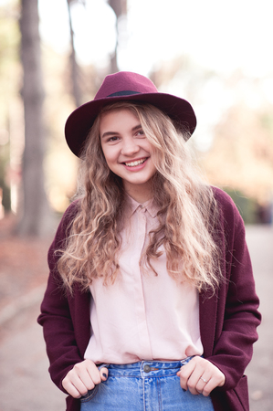 Autumn portrait of smiling blonde teenage girl 14-16 year old wearing stylish winter jacket and felt hat outdoors. Looking at camera. Good mood. Positive emotions.