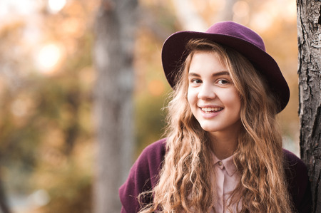 Smiling teenage girl 14-16 year old wearing stylish felt hat posing in park. Looking at camera. Closeup autumn portrait.