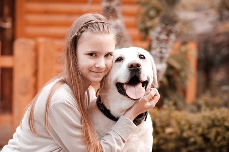 Smiling teen girl 14-16 year old holding labrador dog outdoors. Looking at camera. Happiness. Friendship. Stock Photo
