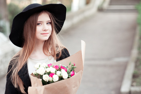 Beautiful teenage girl 14-16 year old holding flower in paper outdoors. Looking at camera. Stock Photo