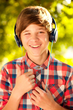 Smiling kid boy 14-16 year old listening to music outdoors. Childhood. Enjoyment. Stock Photo