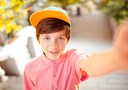 Smiling kid boy 14-16 year old taking selfie outdoors. Childhood. Looking at camera. Stock Photo