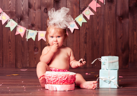 1: Baby girl 1 year old eating birthday cake in room. Birthday party. Looking at camera. Childhood.