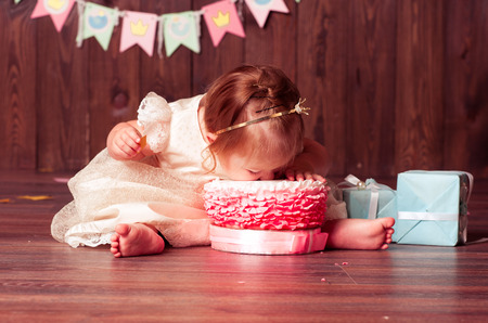 1: Baby girl 1 year old celebrating first birthday in room. Eating cake. Birthday decoration. Childhood.