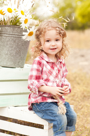 cute baby girl sitting on crates with decorations outdoors stock