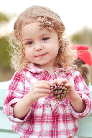 Kid girl 3-4 year old playing with fir cones outdoors. Looking at camera. Childhood.  Stock Photo