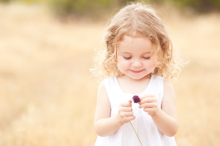 Cute baby girl 2-3 year old holding flower in meadow outdoors. Childhood.