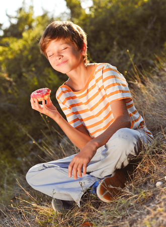 Happy kid boy 12-14 year old eating donut outdoors. Eyes closed. Sunny day.