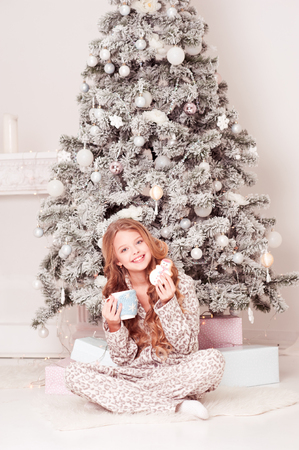 Smiling teenage girl 12-15 year old sitting under Christmas tree with presents. Drinking tea and eating cookies in room.