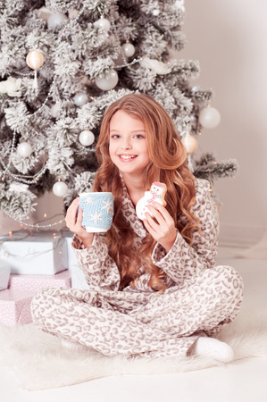 Happy teen girl 10-12 year old having breakfast under Christmas tree in room. Looking at camera. Celebration. Christmas eve.  Archivio Fotografico