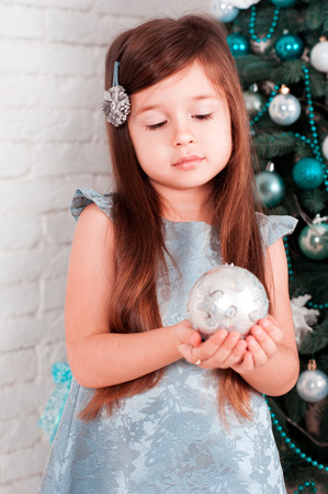 Cute girl 4-5 year old holding christmas ball over christmas tree in room. Wearing stylish silver dress. Looking down. Celebration.  Stock Photo