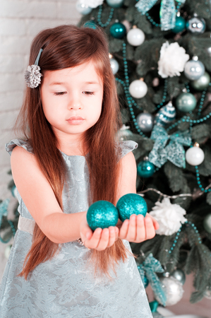 Cute baby girl 3-4 year old holding christmas balls in room. Celebration. Child decorating christmas tree. Childhood.