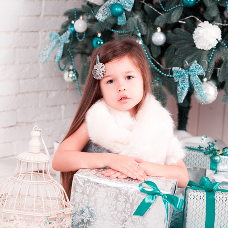 Beautiful kid girl 4-5 year old sitting with christmas decorations and boxes on white wooden floor. Posing in room. Looking at camera. Childhood. Merry christmas. Happy new year. Stock Photo