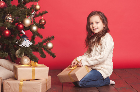 Cute baby girl 4-5 year old opening christmas presents under christmas tree in room over red. Wearing white knitted sweater.  Stock Photo