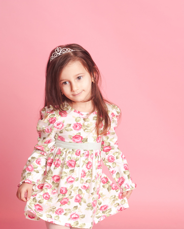 Little girl 4-5 year old posing in room over pink. Wearing trendy floral dress.