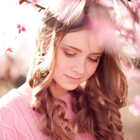 Beautiful teen girl 14-16 year old with curly hairstyle posing in peach flowers outdoors. Smiling child.