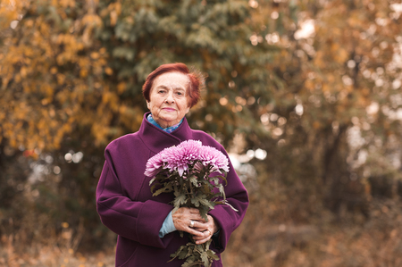 Smiling senior woman 70-80 year old wearing stylish winter jacket holding flowers outdoors. Looking at camera. Archivio Fotografico