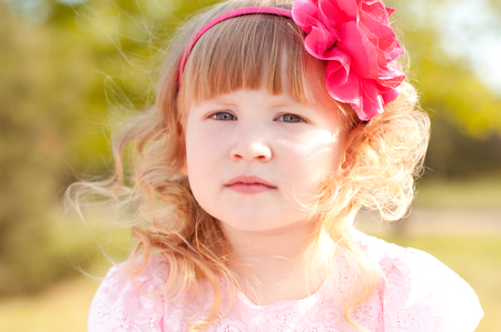Cute kid girl posing outdoors. Wearing hairband with pink flower. Childhood.  Stock Photo