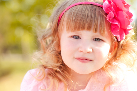 34: Smiling kid girl 3-4 year old wearing floral hairband outdoors. Looking at camera. Childhood.