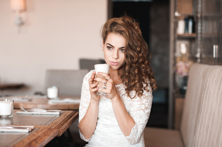 Beautiful girl 20-24 year old holding cup of coffee sitting in cafe. Stock Photo
