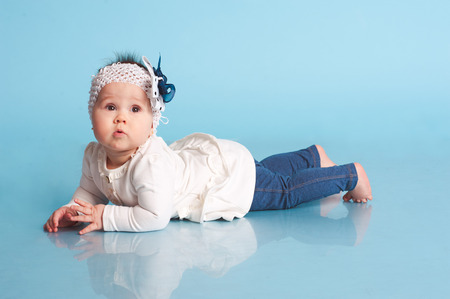 Funny child girl standing in room over blue. Doing first steps. Wearing trendy clothes. Looking at camera. Childhood. Stock Photo